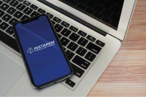 Instarem app on phone on top of laptop