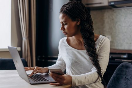 Woman on laptop holding credit card